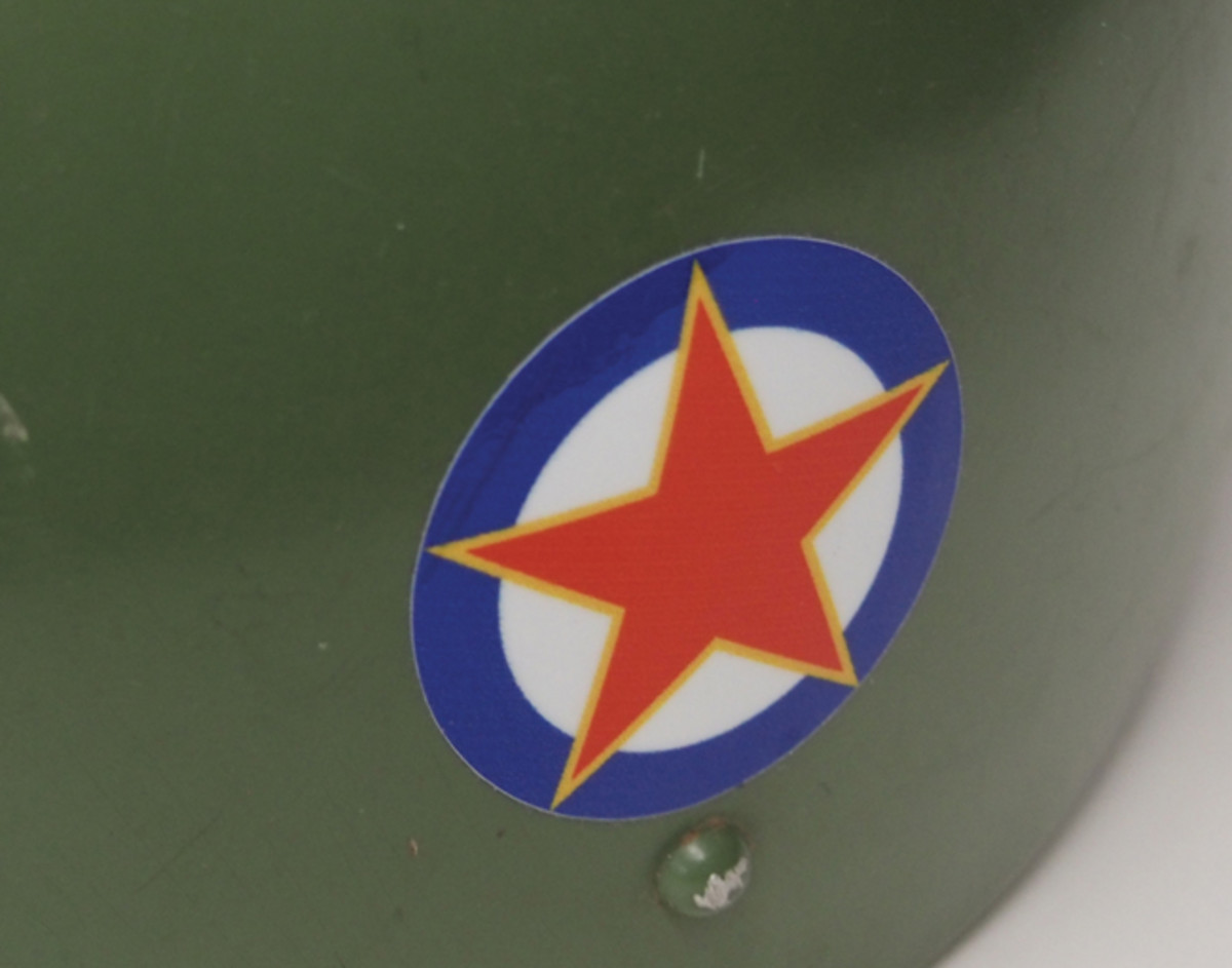 "Where the issue of ""cockade vs. roundel"" gets murky is in how some military helmets are adorned with decals or other insignia that is not technically a cockade but is still ""round"" in shape. This Yugoslavian paratrooper helmet even features the Communist era ""roundel"" that was used on its military aircraft. However, technically it might be called ""insignia"" rather than roundel as military tradition still deems that roundels are vehicle – not headgear – insignia."
