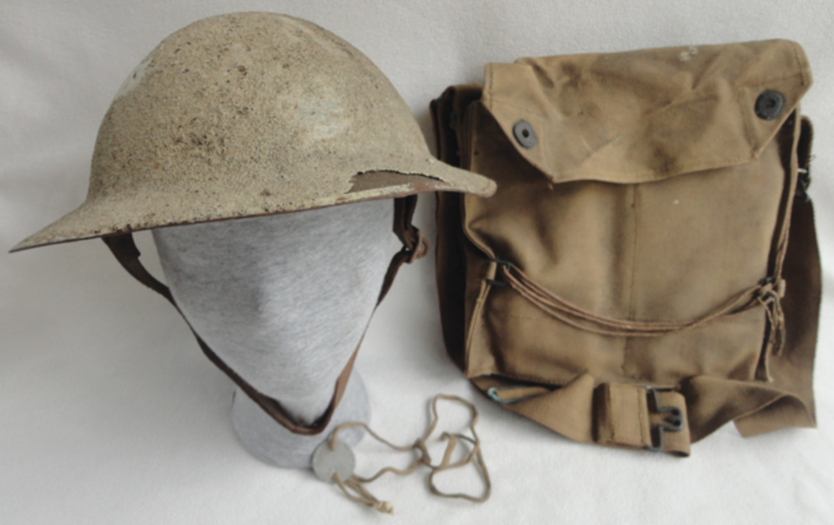 "Niccum's white-painted helmet and gas mask bag. The bag has Niccum's name and ""MG Co."" written on it."