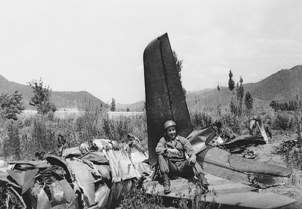 Unknown soldier sitting on wreckage of an American plane, Korea, 1951