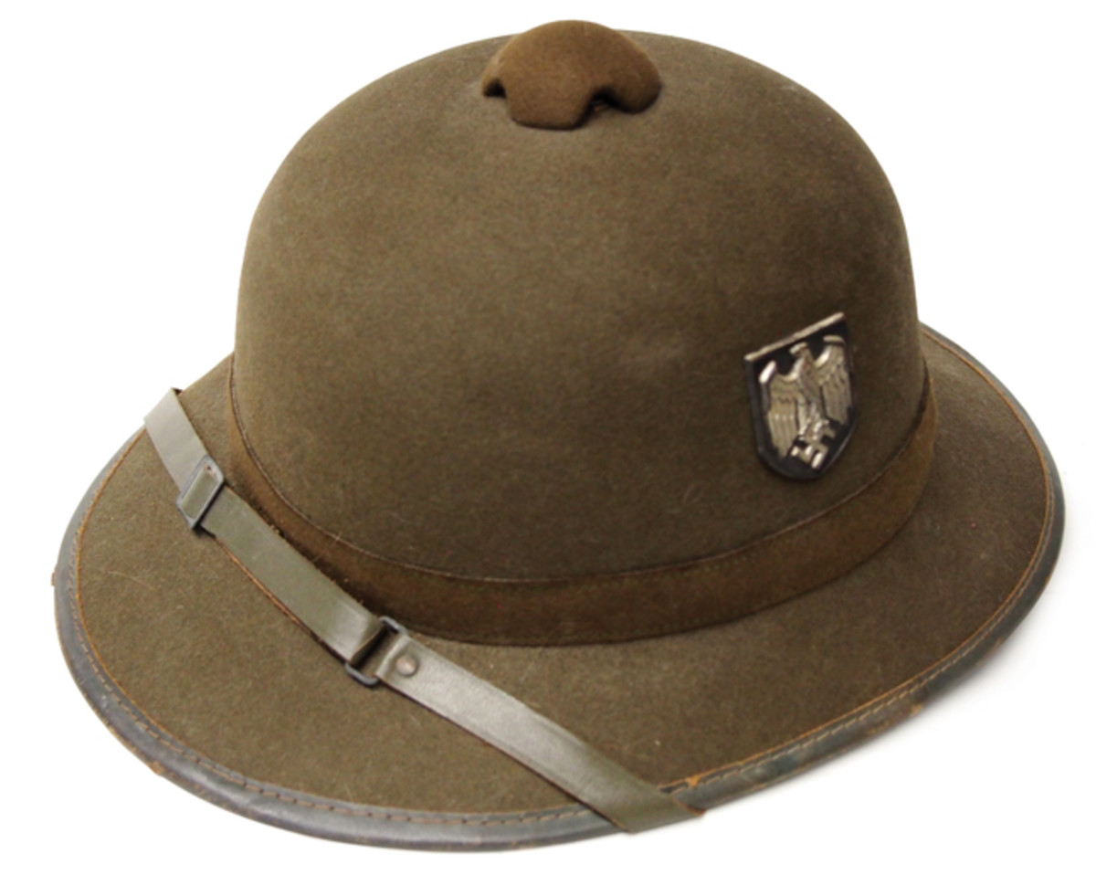 "The so-called ""Second Pattern"" German tropical helmet of World War II. Many published sources suggest these helmets were never intended for use in Africa, but it could be that the production of these only picked up by which time the war in Africa was already winding down. There is little other reason to explain why helmet makers were producing cork-, straw-, and felt bodied helmets."