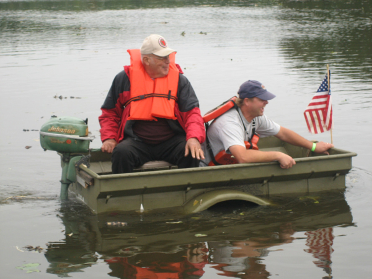 "Boys will be boys. Members of the MVPG of Spooner, WI prove that even a ¼ ton Jeep trailer can be amphibious with some outboard ""motor-vation."""