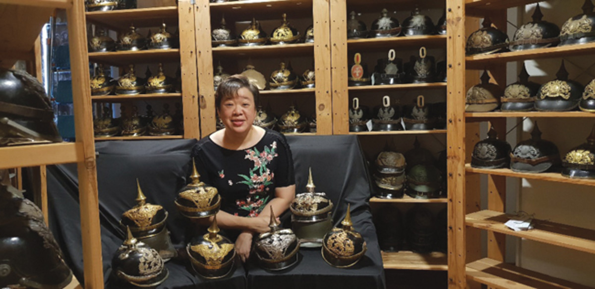 Amy Bellars with her vast collection of Imperial Pickelhauben German WWI steel helmets, and WWII-era Japanese helmets.