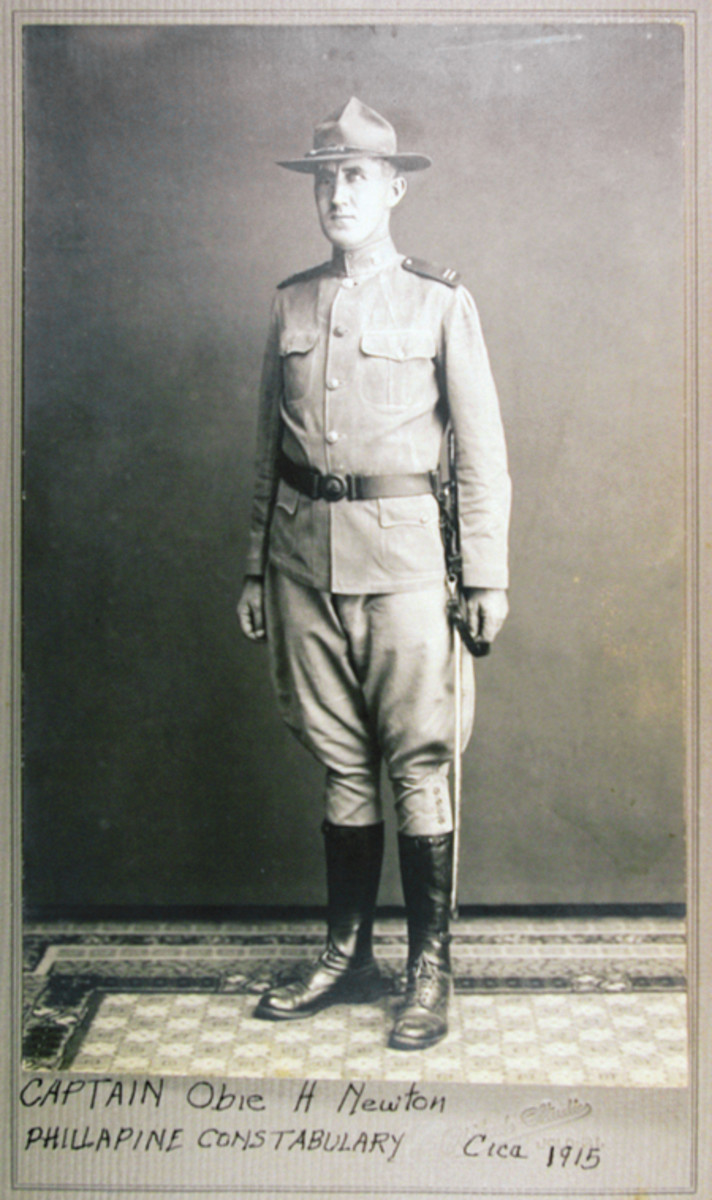 "Full length photo of Capt. O H Newton in full uniform wearing the sword pictured in this article on a Philippine Constabulary leather belt. Newton, who stood 6' 4"", must have seemed a giant among the Philippine natives."