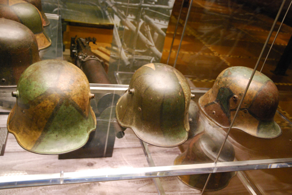 """Three German World War I """"coal scuttle"""" helmets with camouflage paint."""