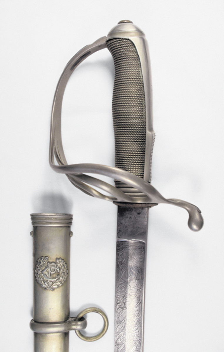 "A close up view of the hilt and scabbard throat reveals the intricate engraving on the blade and the ""PC"" marking on the scabbard."