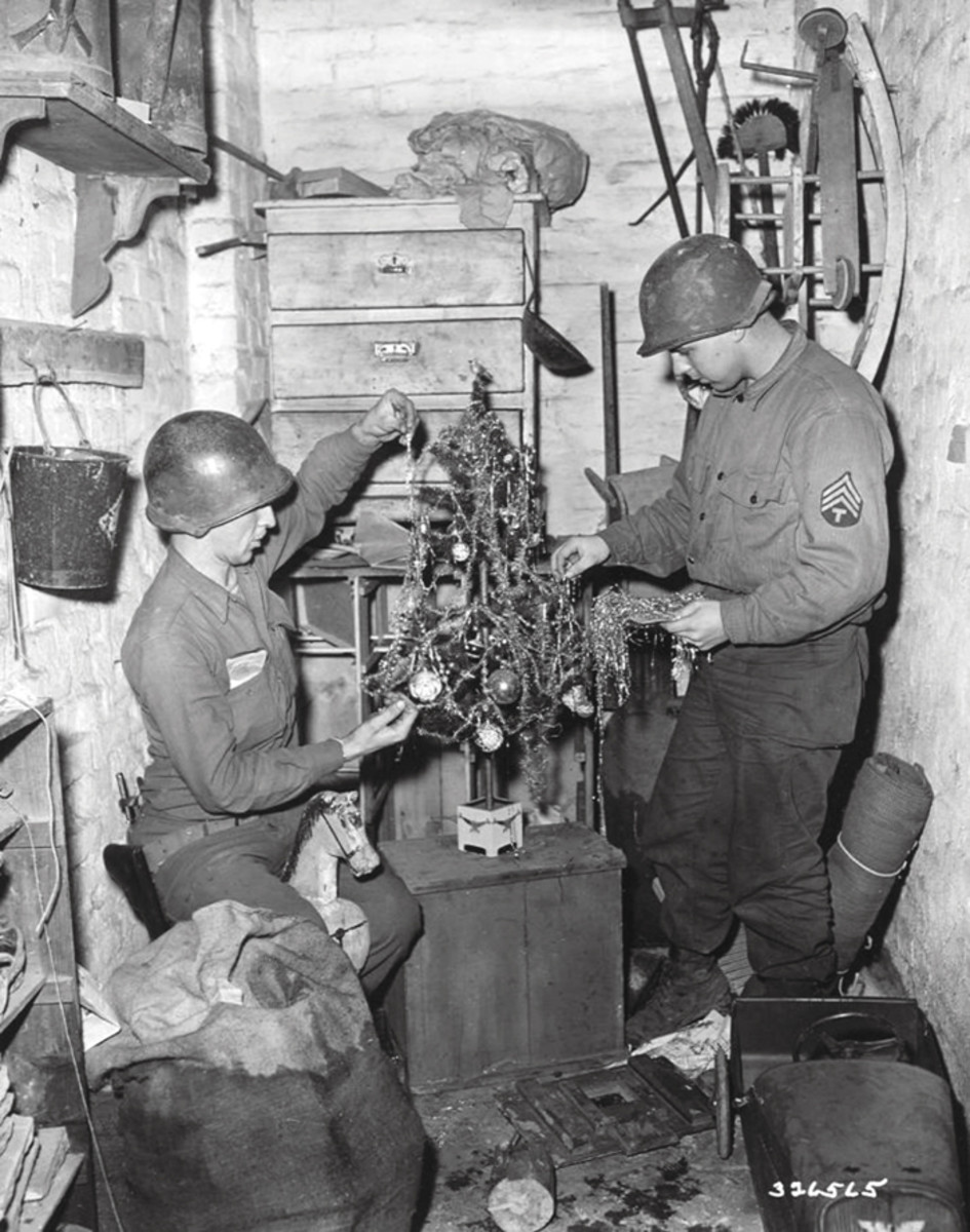 84th Training Command. Two GIs of 84th Training Command decorate a Christmas tree in cellar of a home in Geilenkirchen, Heinsberg, Germany. December 1944.