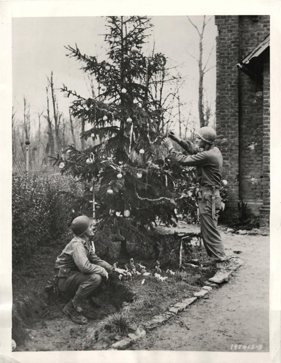 Private Robert Frick and Pvt Robert Engelman, both of Philadelphia, decorate a Christmas tree with trimmings from German homes in the captured town of Heren, December 21, 1944.