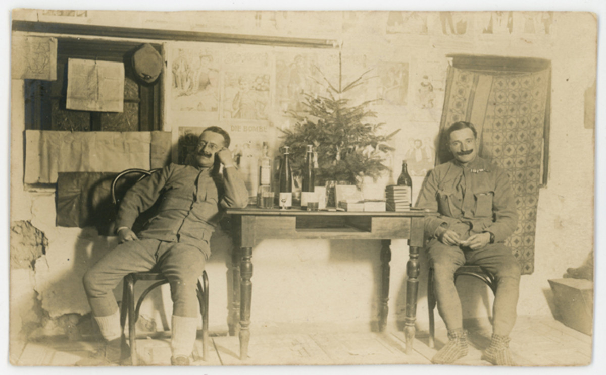 "Real photo postcard shows two Austrian soldiers posed with a tabletop Christmas tree. The message on the reverse sends good wishes for 1916. The postcard was postmarked on December 27, 1915, by the Austrian Landwehr Infantry Regiment ""Neusandez"" No. 32."
