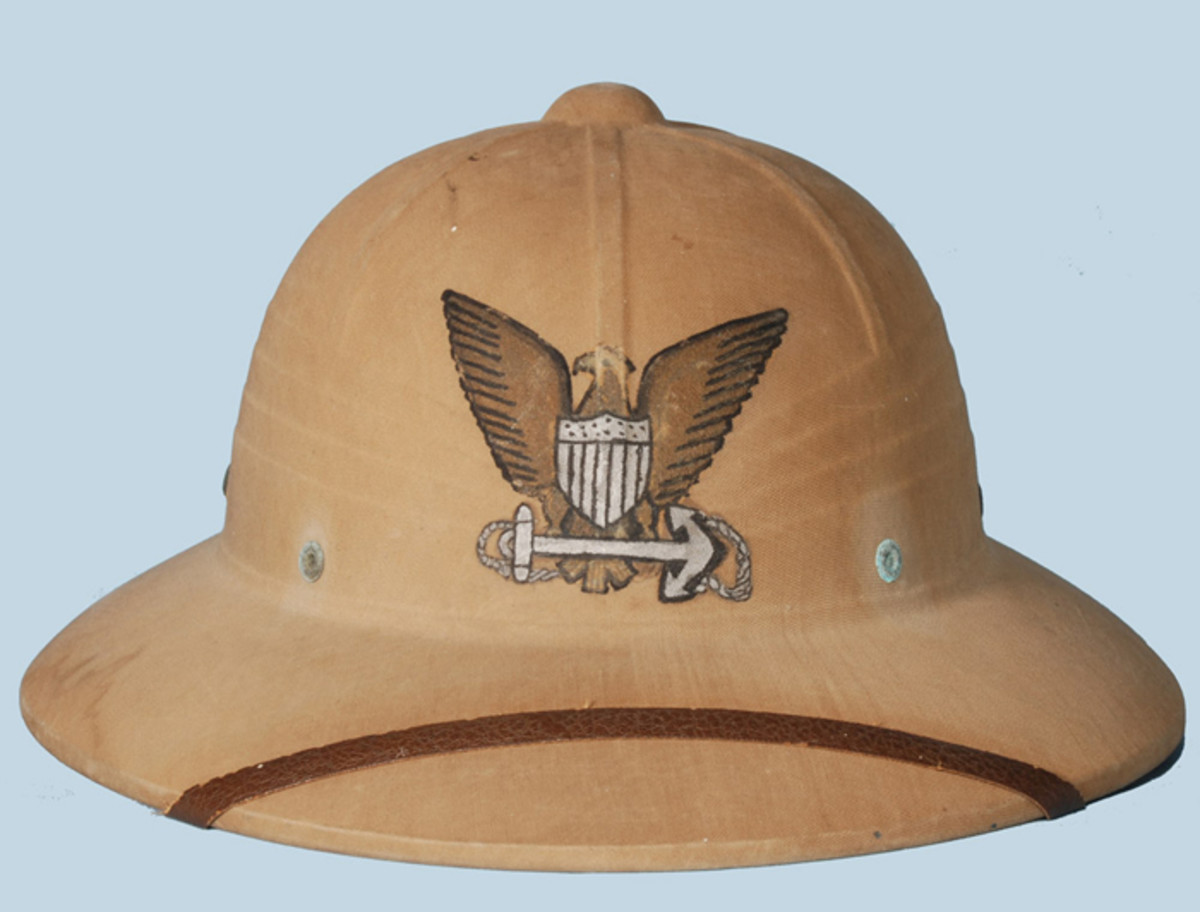 """An interesting piece of wartime """"soldier"""" art – or in this case """"sailor"""" art. This early Hawley-produced helmet lacks the front grommet for the attachment of the insignia, and the crafty owner instead painted on the U.S. Navy insignia."""