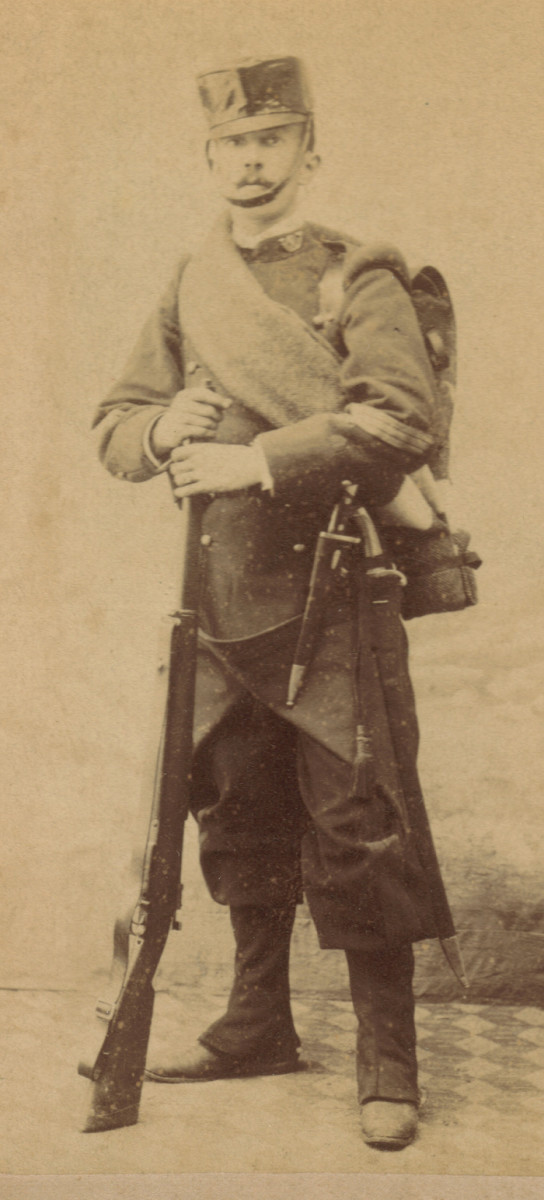 "A cabinet card image of an NCO of the 20th. Light Infantry, or ""Cazadores"", Battalion ""Manila"" in full marching order, late 1890s. The Model 1886 Infantry greatcoat has a green collar with the hunter's horn insignia with unit number in the twist. The shoulder wings are also green. A black  oilcloth field cover protects his shako."