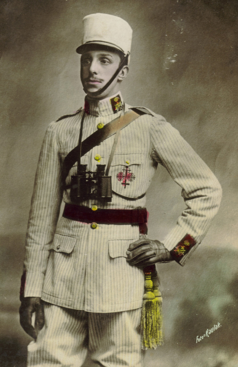 A commercial postcard with a portrait of His Majesty Don Alfonso XIII, King of Spain, wearing a General's Peninsular rayadillo campaign uniform complete with scarlet and gold sash. The General's rank insignia on the collar and cuff is on a scarlet wool backing, used only for a short time between 1911 and 1914. The left pocket of his tunic is embroidered with the combined emblems of four  different knightly Military Orders to which he belonged.
