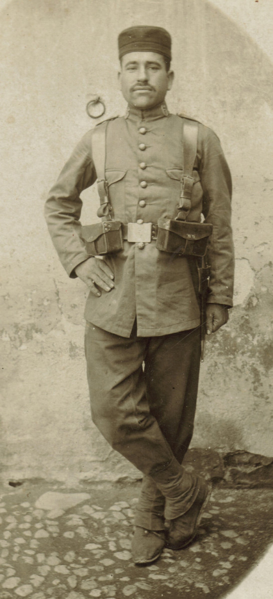 "A Private from the 6th Infantry Regiment ""Saboya"". He is attired in the Model 1914 tunic and trousers, Spain's first 'camouflaged' field uniform. The ""ganaderos"" trousers have integral leggings and the blue and red wool fatigue cap was still worn with this uniform."