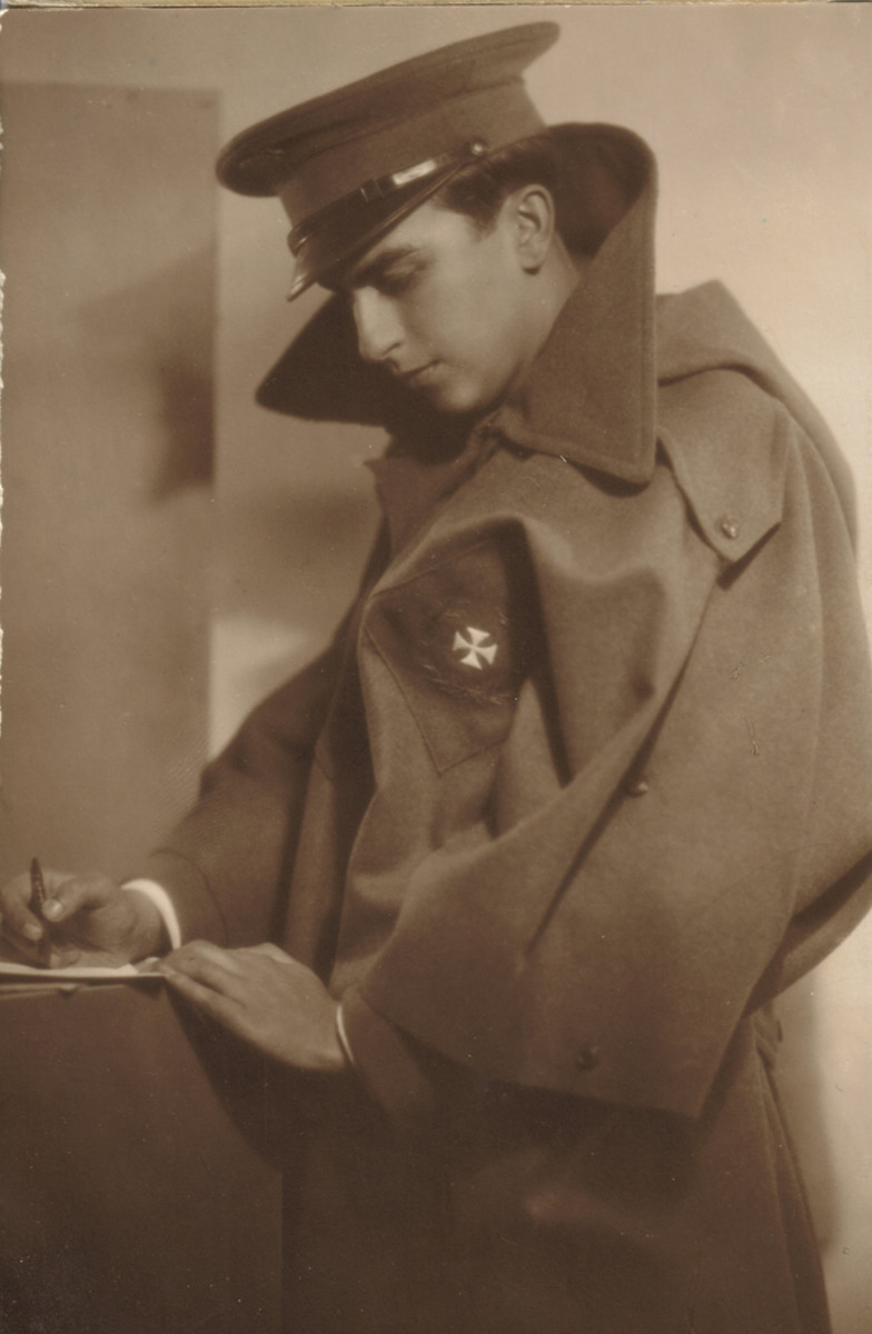 "A soldier of the Medical Department  poses for an artistic portrait wearing the olive wool poncho known as the  ""capote-manta"". The branch of service was embroidered on a diamond shaped olive wool background and sewn on the left chest. The visor cap was introduced for enlisted men about 1930."