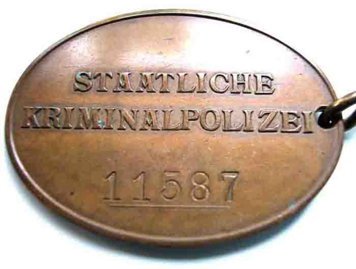 A Kripo warrant disk belonging to a criminal police officer (Kriminalpolizei) of Third Reich-era Germany, part of the set that realized $18,000 at Grenadier Auctions.