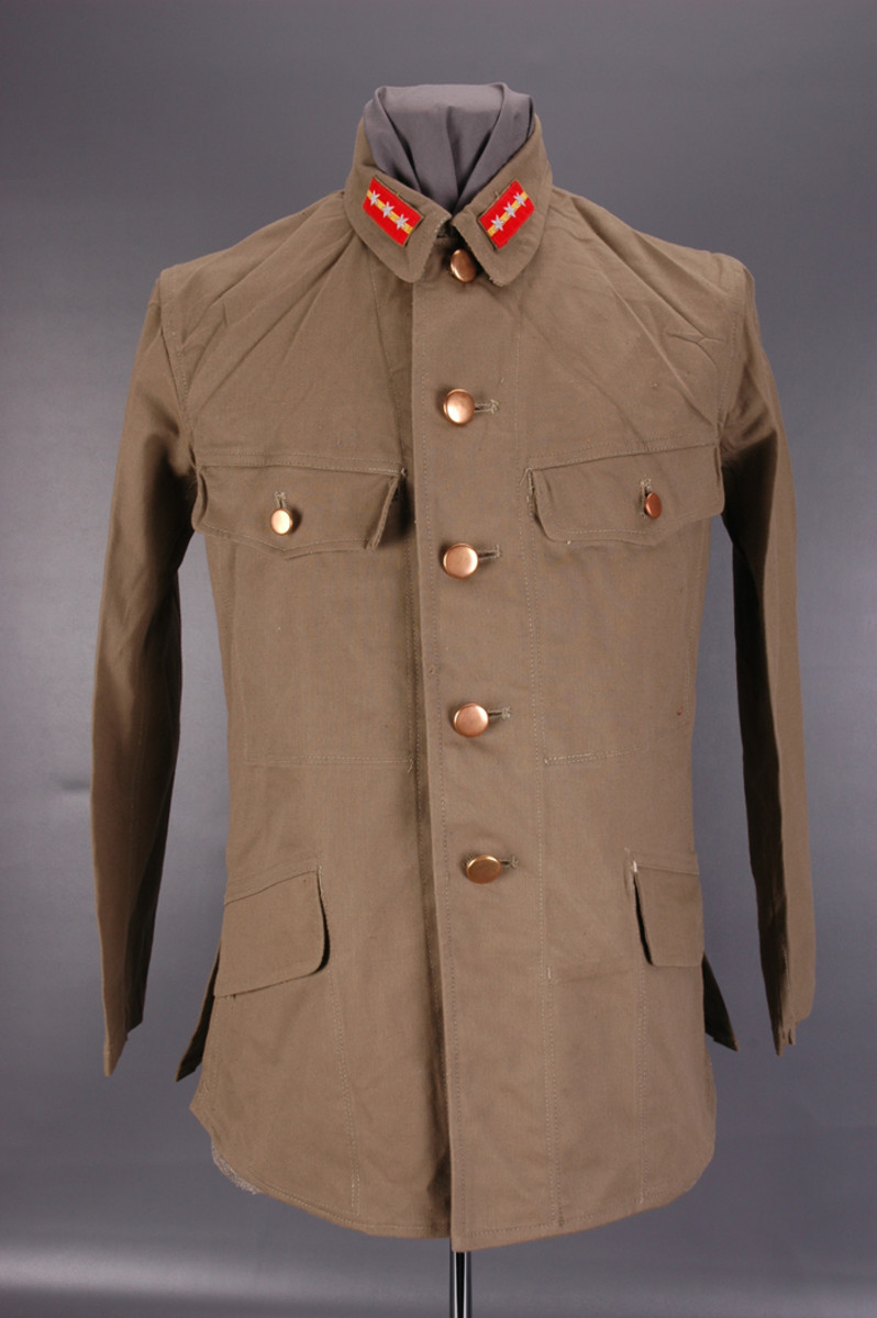 The Type 98 tunic, whether winter issue or summer issue like this cotton Sergeant Major's example, is recognizable by the stand-and-fall collar with rank patches and four exterior pockets. The top two pockets each have a scalloped flap with one button while the bottom two slanted pockets each have a simple straight-cut flap with no button.