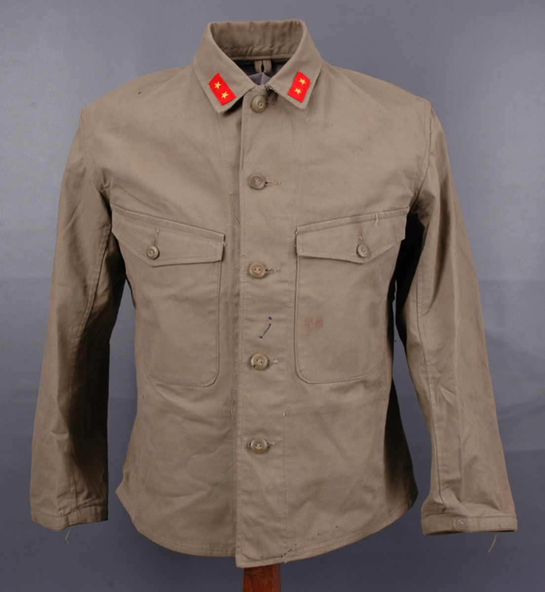 "Kesenfuku was a produced in 1945 as a home defense or ""last-ditch"" tunic. Features that make it easily recognizable include the stand-and-fall collar (shown here with Type 98 Private First Class insignia) and the two large breast pockets, each with a pointed flap and single button. On the wool version, these pockets were usually concealed with only the flaps visible whereas on the cotton version, they were sewn as patch pockets."