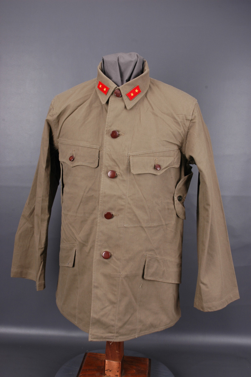 The Japanese Army issued at least three versions of tropical tunics during WWII. While strongly resembling a Type 98 tunic made of cotton material, a tropical tunic is readily recognized by the buttoned vent located under each arm.