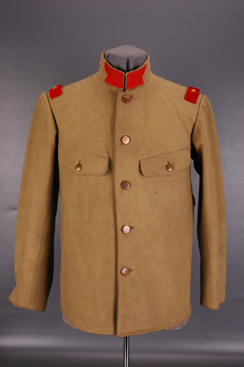 Type 5 tunic is recognizable from the standing collar with swallow-tail collar patches and two inset breast pockets with scalloped, buttoned flaps. The buttons on this mustard-colored woolen Private Second Class' tunic are bronze-colored tin.