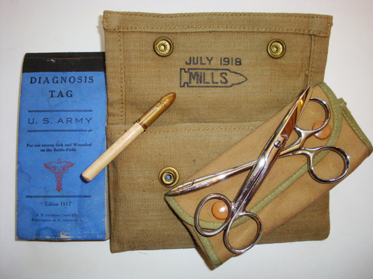 At left, the enlisted medical pouch hung from the right front of the belt and contained one book of diagnosis tags, pencil with metal cap, and a case containing  dressing scissors and forceps.