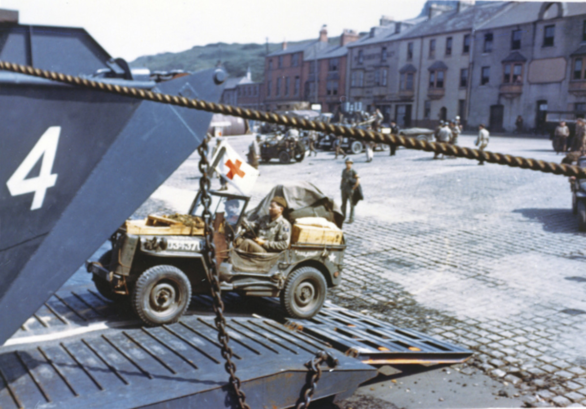 Jeeps driving into the open doors of an LCT (Landing Craft Tank) at a port in Britain in preparation for D-Day.