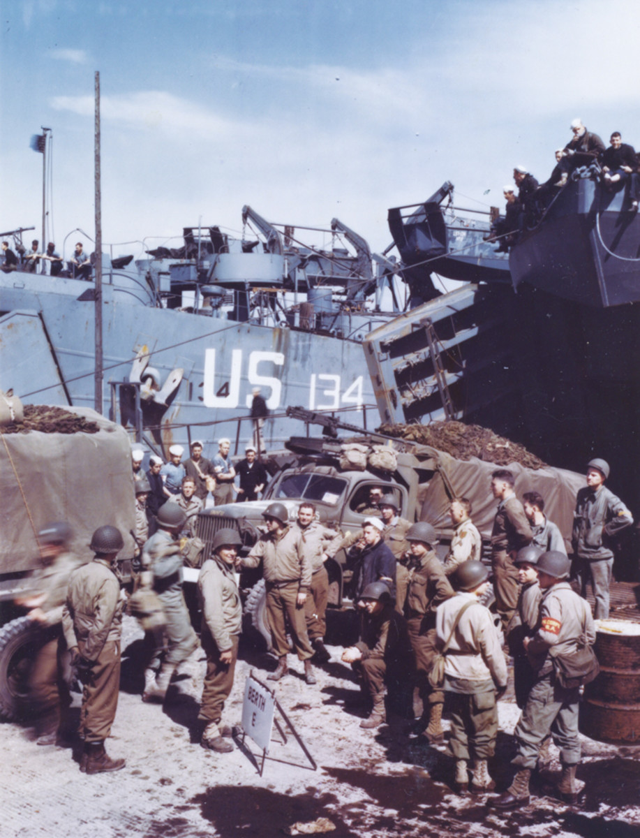 Trucks which will carry supplies to front line troops when the assault against Hitler's Europe begins, are being loaded on an LST in a British port.