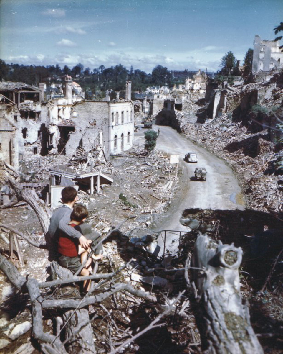 Two children use a the vantage point of St Lo château (or rather the ruins of) to look on at a US Jeep following a French Citroen as they drive down rue des Noyers.