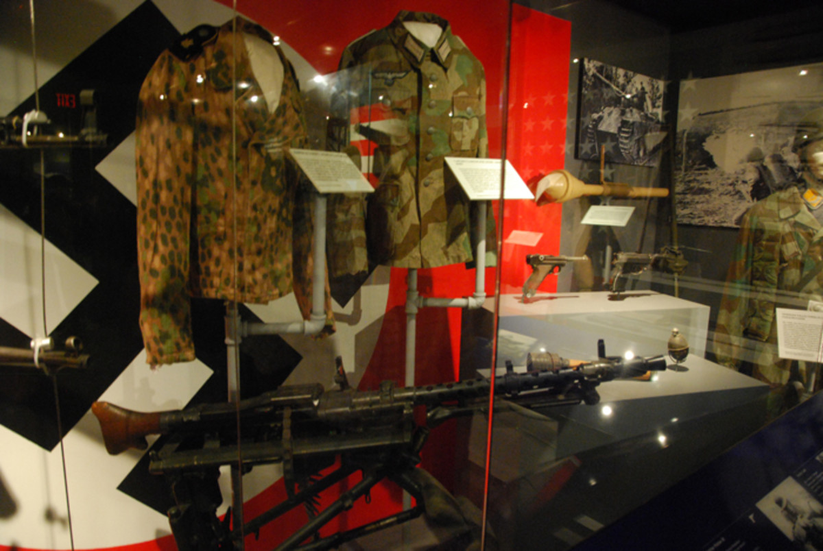 On display are German camouflage tunics and other small arms including an MG-34, Panzerfaust, Luger, and P38 pistols and various grenades.