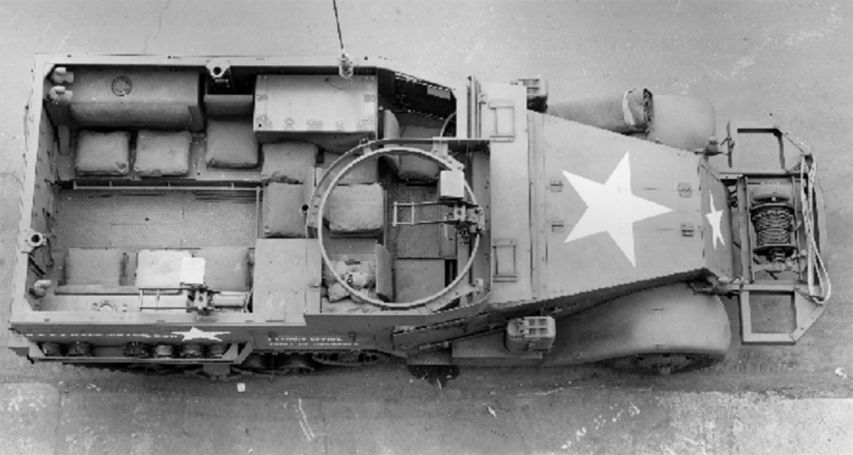 By comparing this overhead view of a M2A1 to the earlier overhead view of a M2, we can see how the entire interior layout was revised. The SCR-528 radio set has been installed in the stowage compartment behind the driver. The stowage compartment on the other side has been relocated to accommodate the ring mount, and fixed sockets for machine gun pintles have been installed.