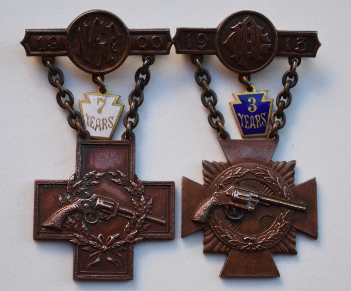 A comparison of Type 1 and Type 2 revolver qualification badges. The badges used a keystone pendant showing years of qualification with white for expert, red for sharpshooter, and blue for Marksman. After 1923, the decision was made to forgo the Commonwealth's own marksmanship awards and to use U.S. Army qualification badges instead.