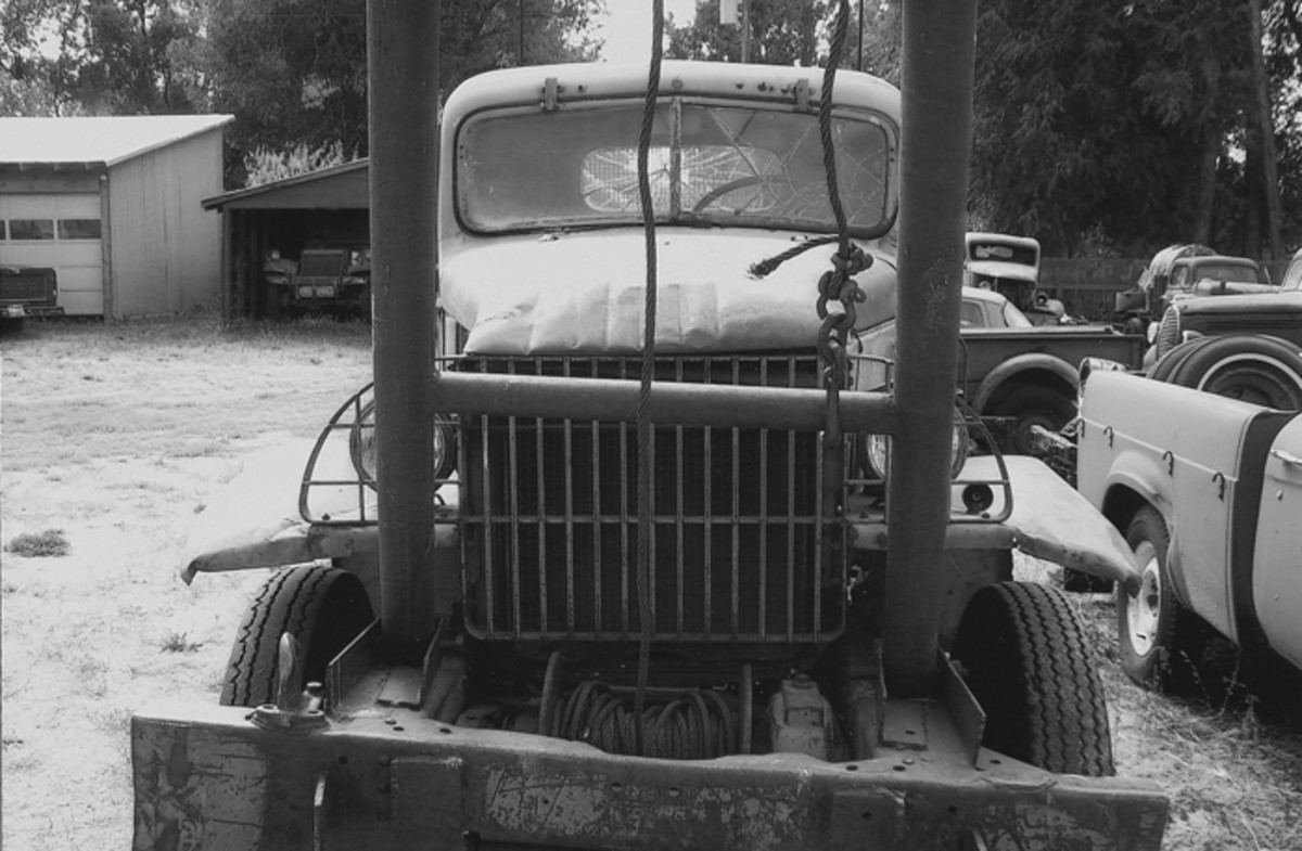 This battered old boom truck, which is still in use, has the late model single bar grill. Note the thin cross-grille tie bar between the fenders.