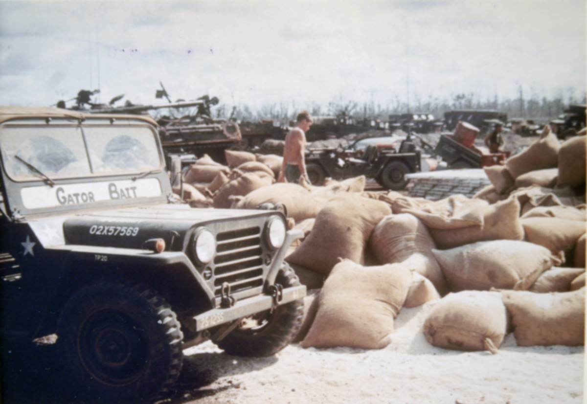 A 1969 M151 in the foreground, along with a second MUTT in the background, flank loads of rice in the Fish Hook area of Cambodia. The MUTTs, along with the M88 in the left background, were assigned to First Battalion, 27th Infantry in May 1970.