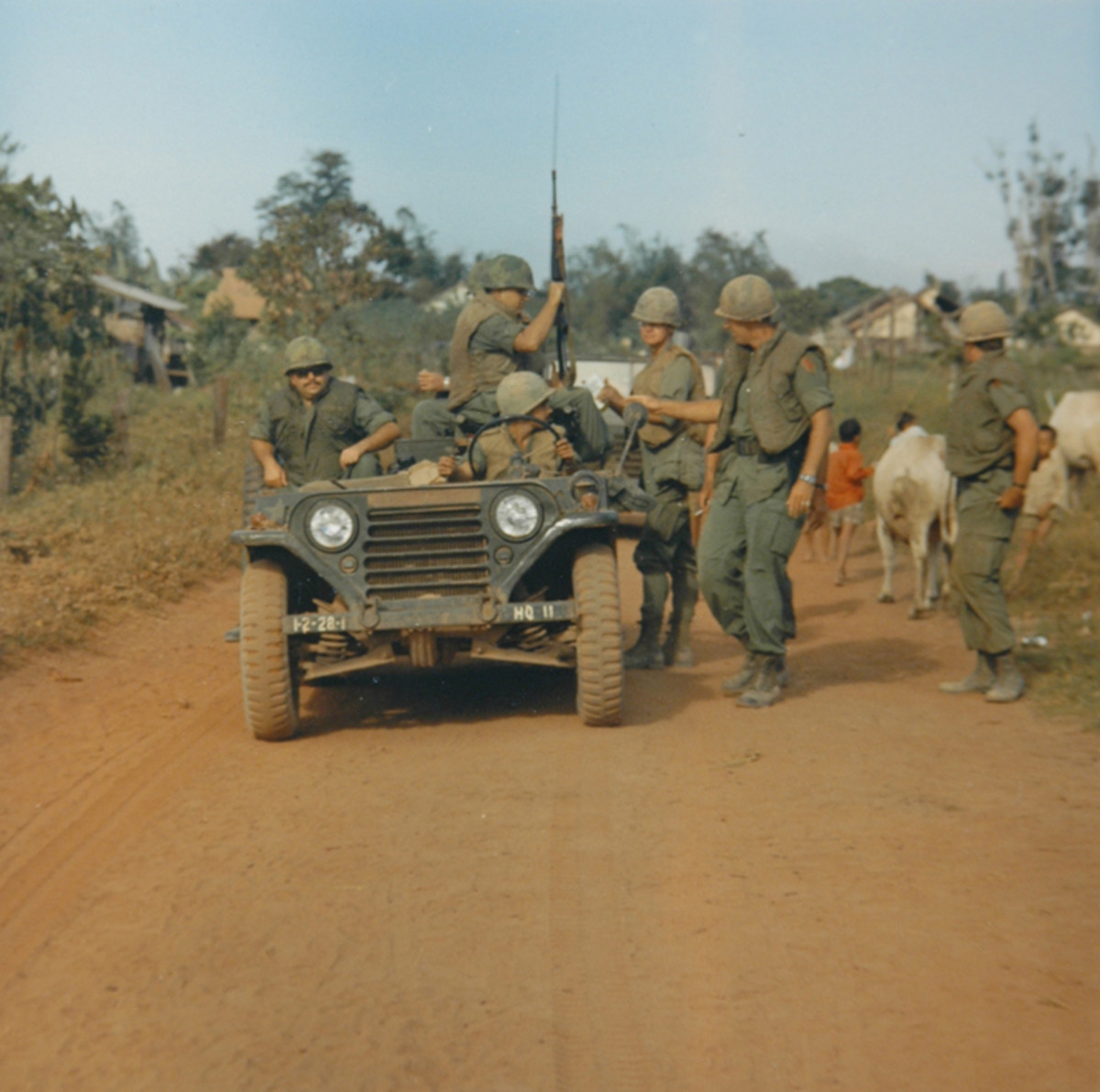 A First Infantry Division patrol, utilizing a M151A1, patrols a dusty road in Vietnam during 1969. The rear-down stance of the vehicle is indicative of its light load-carrying capacity and independent suspension.