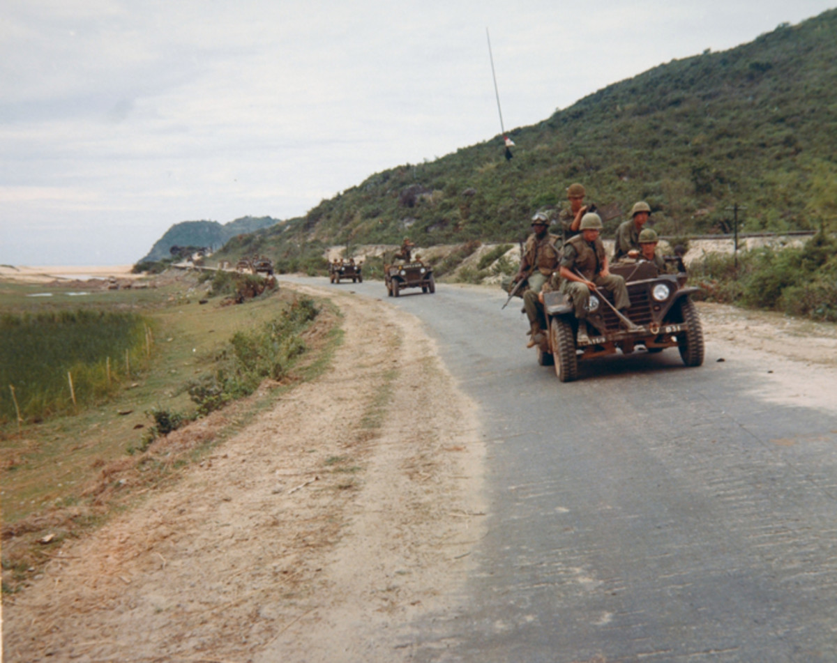 A trio of MUTTs lead a convoy along Route 1 in Vietnam in July of 1967. The vehicles were assigned to First Squadron, Ninth Cavalry, First Cavalry Division (Airmobile). The GI riding on the front bumper of the lead vehicle is carrying a mine detector – an indication of an ever-present danger.