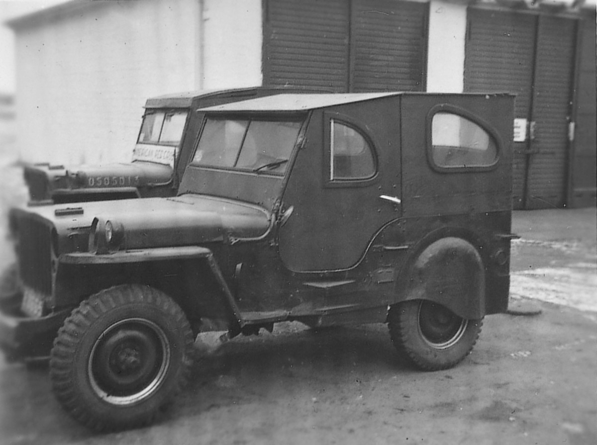 """This modified jeep sports a custom hardtop and rear fender skirts. The jeep no longer sports its registration number on the hood, but rather, an occupation license plate attached to the grille. The jeep behind it does have a USA number on the hood and has """"American Red Cross"""" painted on the lower windshield."""