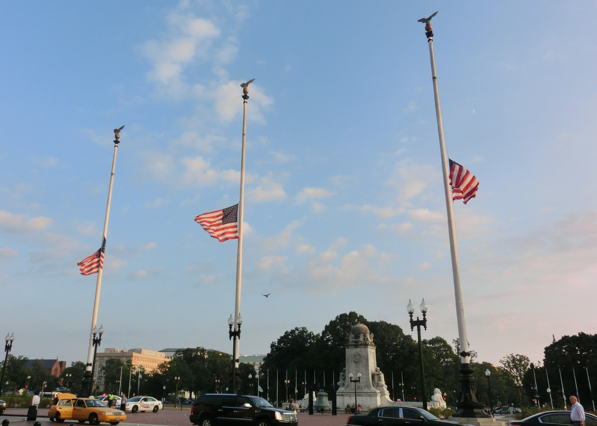 In Washington, D.C., three American flags fly at half-mast on Columbus Circle (outside of Union Station) on Patriot Day 2013. The flags of several US states and territories can be seen also flying at half-mast in the background.