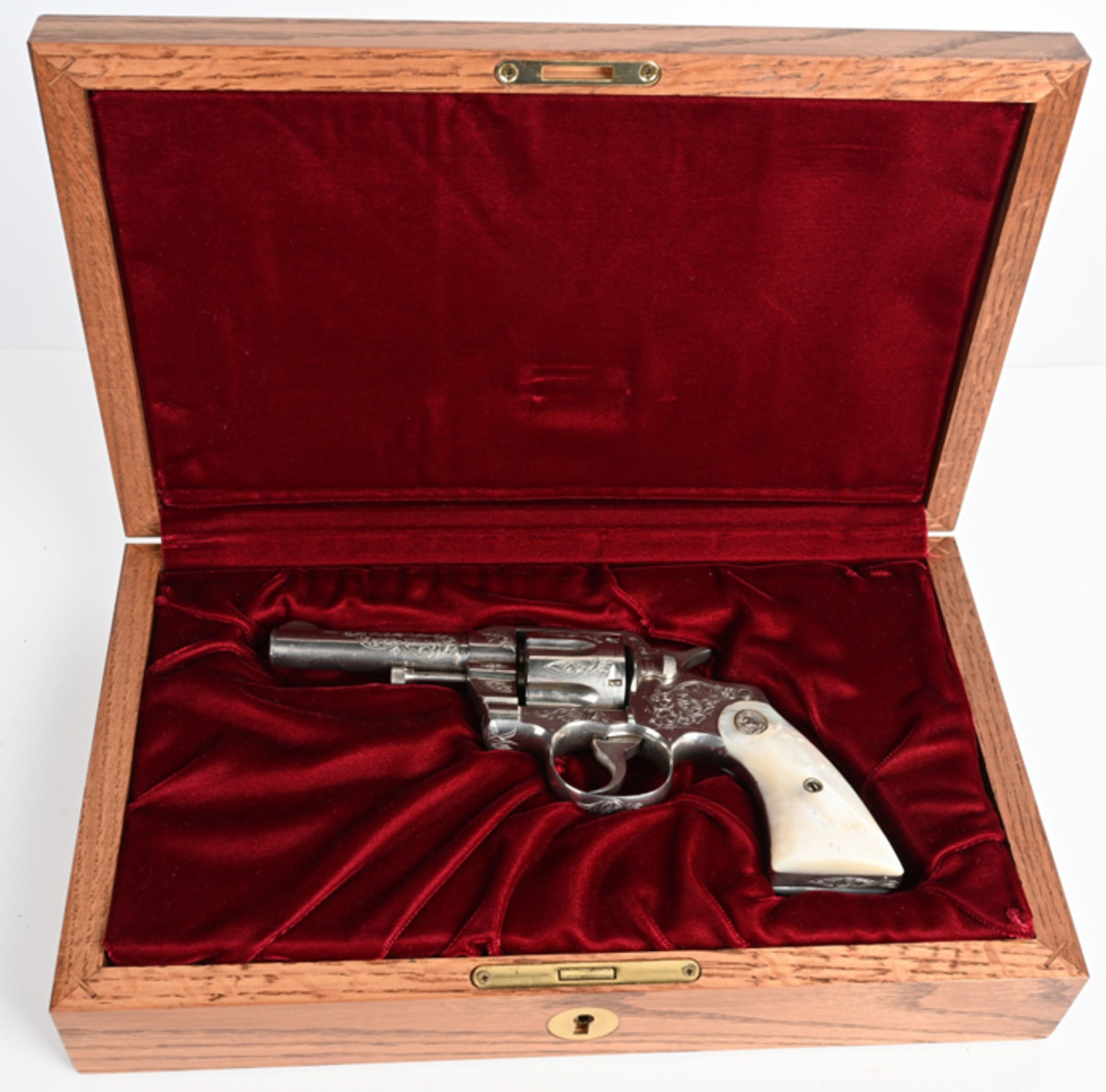 Colt .38-caliber Army Special revolver factory-engraved by William Gough (or his shop). Manufactured in 1924 and shipped to Walter G. Clarke Co., Omaha, Nebraska. Like-new bore and action. Modern Colt walnut display case.