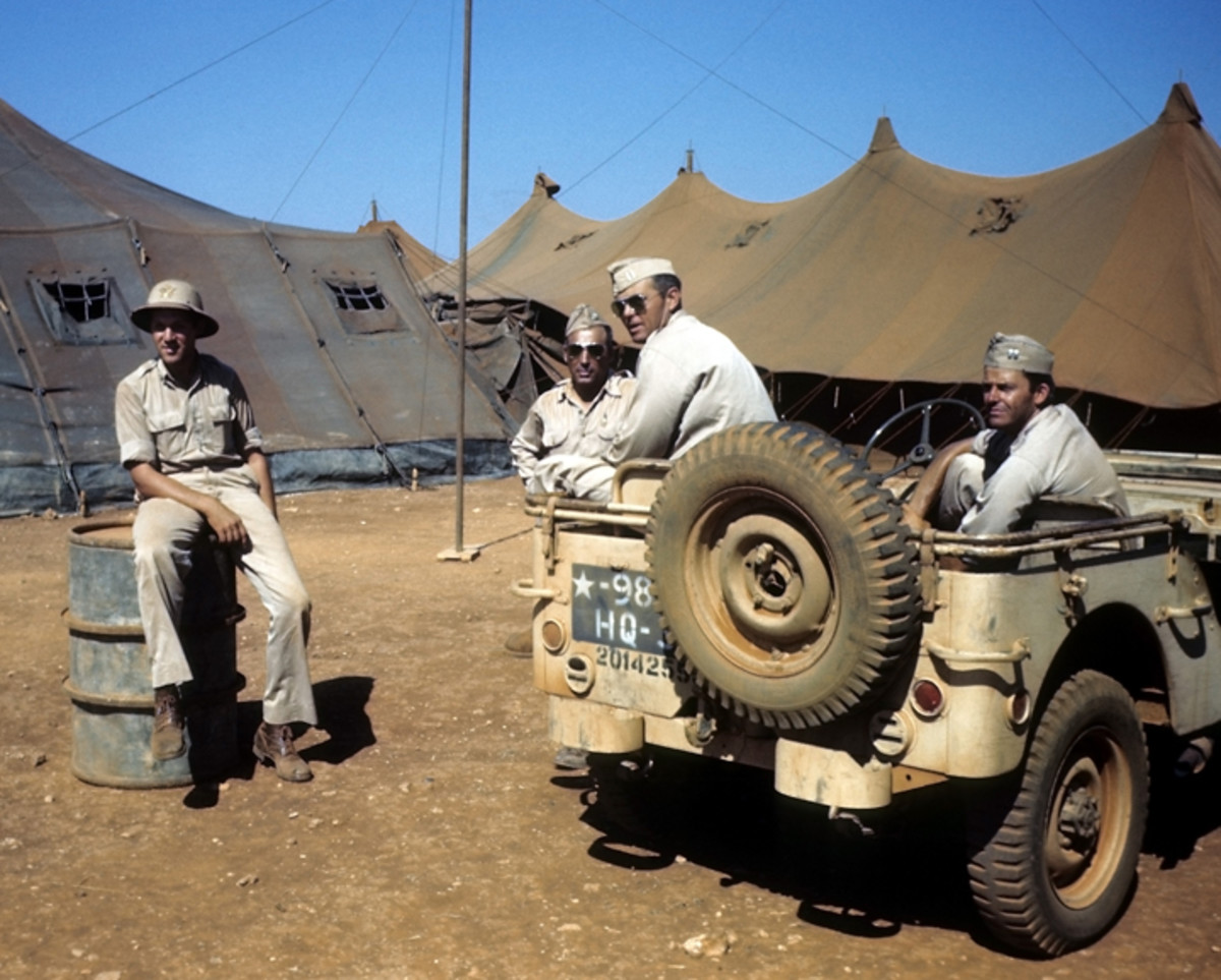 BENGHAZI, LIBYA - AUGUST 8,1943: A view as U.S Soldiers relax on the base at the U.S Air Force base in Benghazi, Libya. Sand-colored jeep numbered USA 201425.