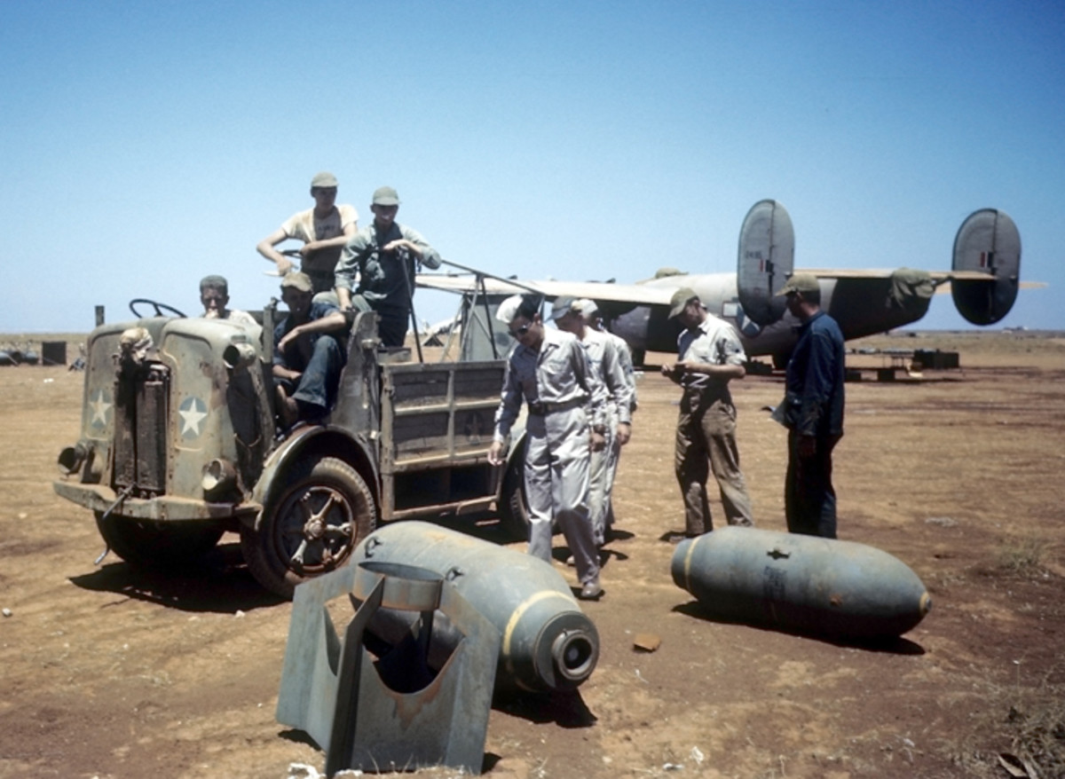 BENGHAZI, LIBYA - AUGUST 16,1943: A view as crew members of the 98th Bombardment Group get a ride back to base on a repurposed FIAT SPA CL39 as bombs lay on the ground at the U.S Air Force Base in Benghazi, Libya.