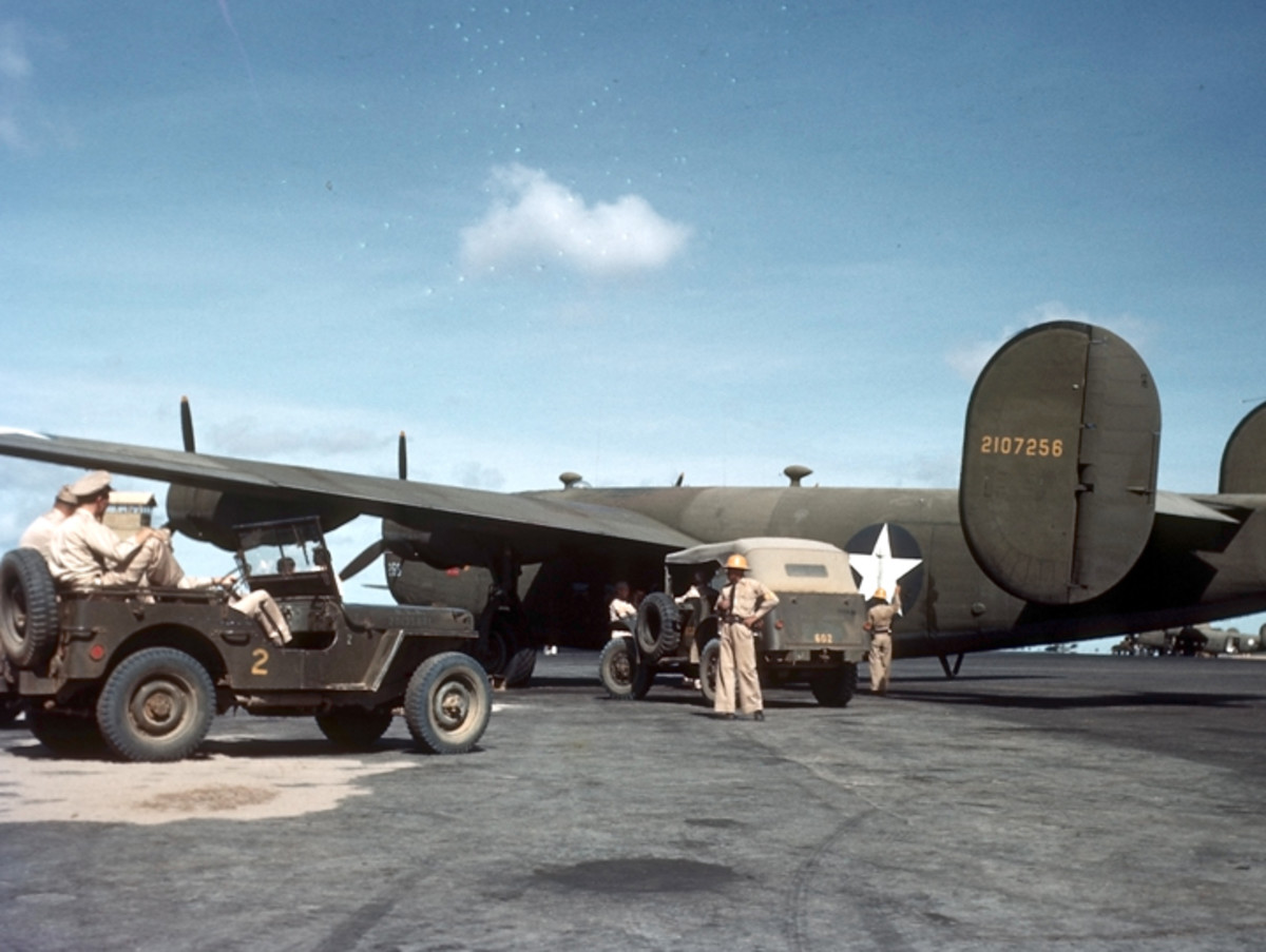 NATAL, BRAZIL - JUNE 1943: A view of a C-87 Liberator Express Transport plane at the Parnamirim airport at the US Army and Air Force base in Natal, Brazil. Notice the much darker shade of OD used on the Jeep and Dodge Command Car. Registration numbers on both vehicles were done in lusterless blue paint.