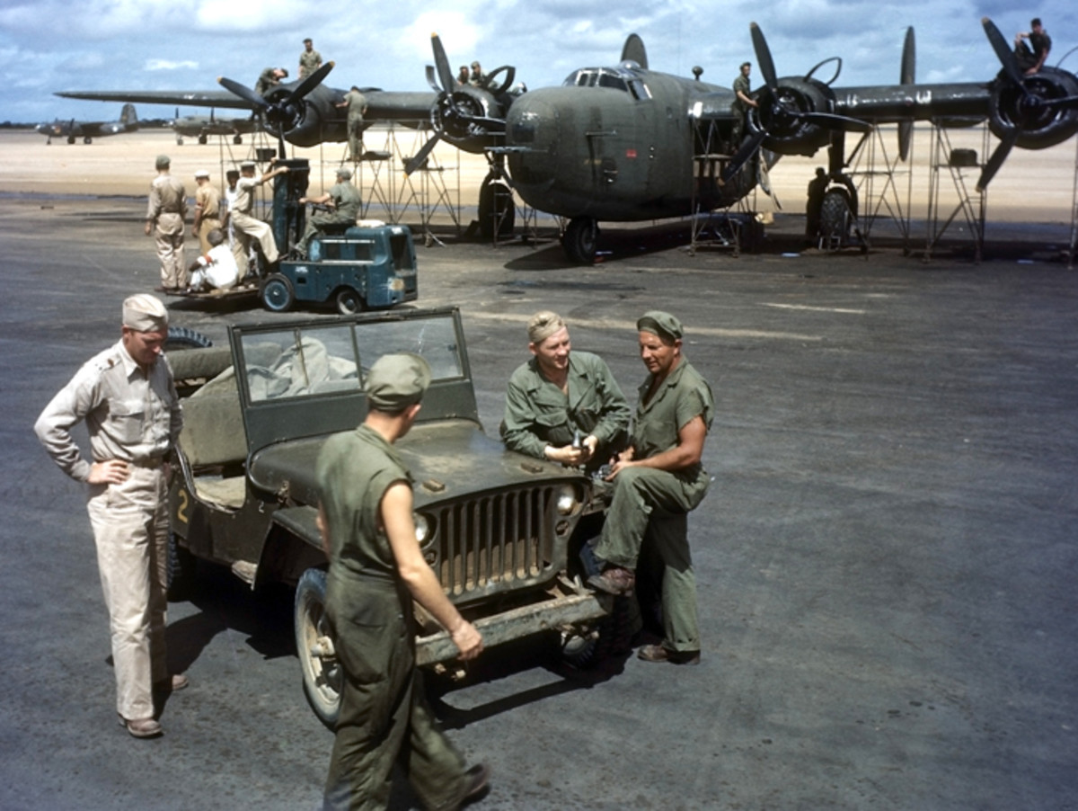 NATAL, BRAZIL - JUNE 1943: A view as US servicemen at the Parnamirim airport at the US Air Force base in Natal, Brazil. The Jeep is painted in a dark OD with blue lusterless registration number. The forklift in the background appears to be painted in strata blue.