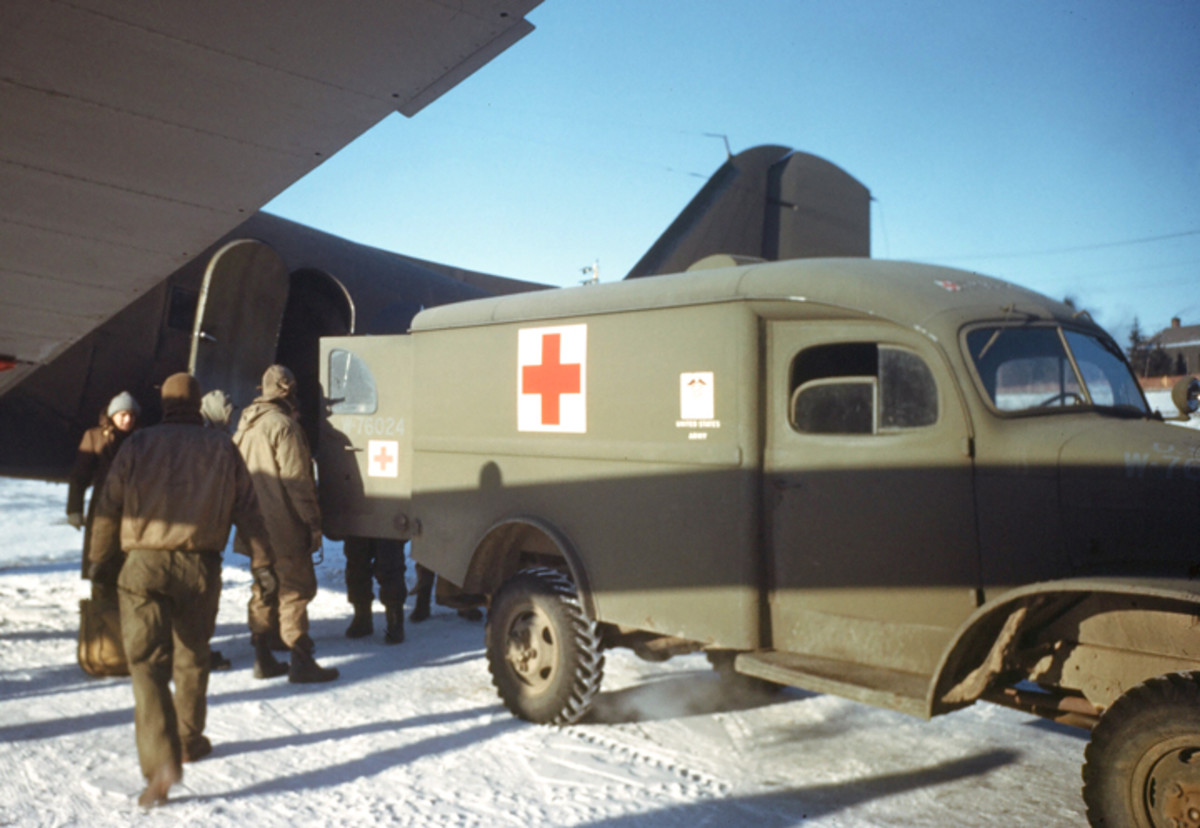 GOOSE BAY, LABRADOR,CANADA- DECEMBER 1942: A 1/2-ton Dodge ambulance (reg.no W-76024 in blue lusterless paint) next to a airplane on the U.S. Air Base in Goose Bay, Labrador, Newfoundland, Canada.