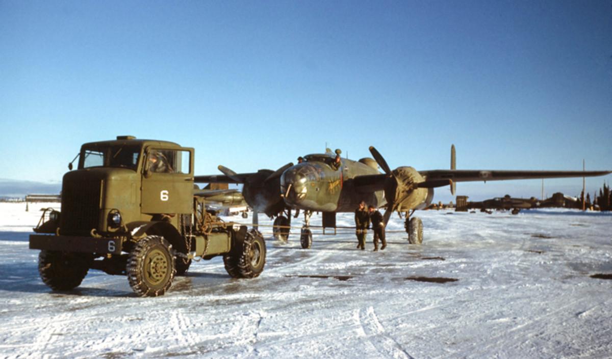 GOOSE BAY, LABRADOR,CANADA- DECEMBER 1942: U.S Airmen use an Autocar U-7144-T 4.5-ton tractor to tow a U.S bomber onto the tarmac on the U.S. Air Base in Goose Bay, Labrador, Newfoundland, Canada.