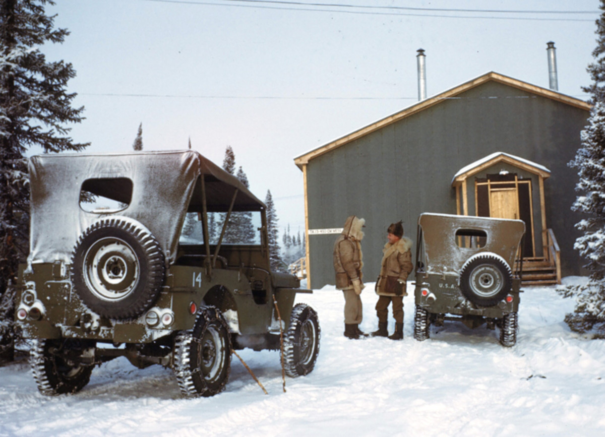 GOOSE BAY, LABRADOR,CANADA- DECEMBER 1942: U.S Airmen stop to talk on the U.S. Air Base in Goose Bay,Labrador, Newfoundland,Canada. The Jeep on the right is a script Ford GPW.