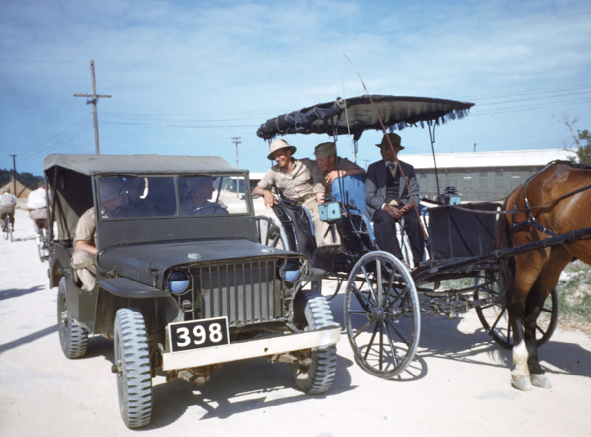 "BERMUDA - CIRCA 1943: US MB ""slat grille"" Jeep (reg no. 2040126) chat with U.S. Navel service men riding in a horse drawn buggy at the U.S. Navel Air Base in Bermuda."