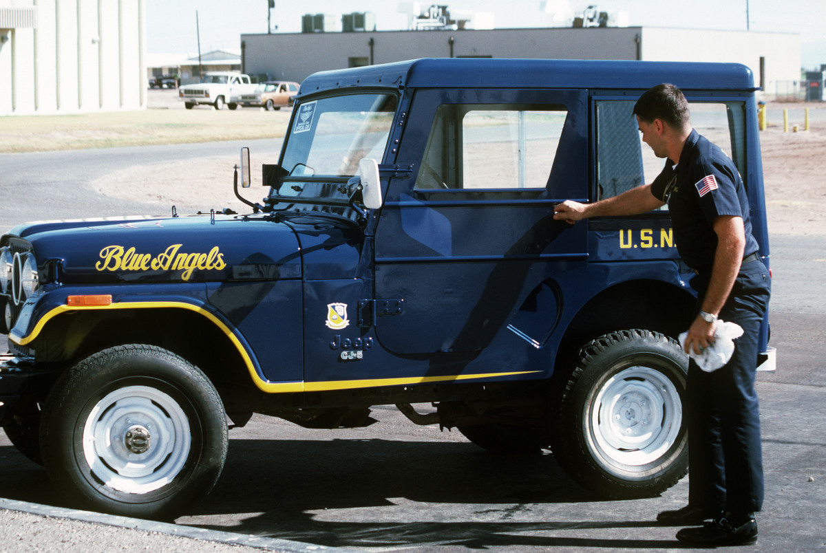 A technician closes the door of an American Motors Corporation CJ-5 Jeep, the official car of the Blue Angels Flight Demonstration Squadron.
