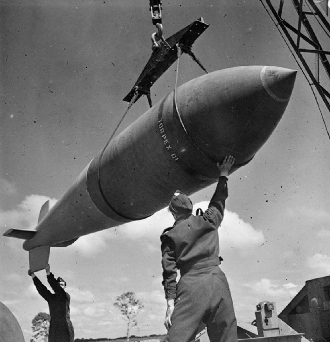 Royal Air Force Bomber Command, 1942-1945. A 12,000-lb MC deep-penetration bomb (Bomber Command executive codeword 'Tallboy') is hoisted from the bomb dump to its carrier at Woodhall Spa, Lincolnshire, to be loaded into an Avro Lancaster of No. 617 Squadron RAF for a raid on the V-weapon site at Wizernes, France. 617 Squadron were unable to bomb the target on this occasion because of low cloud cover, but were to succeed two days later.