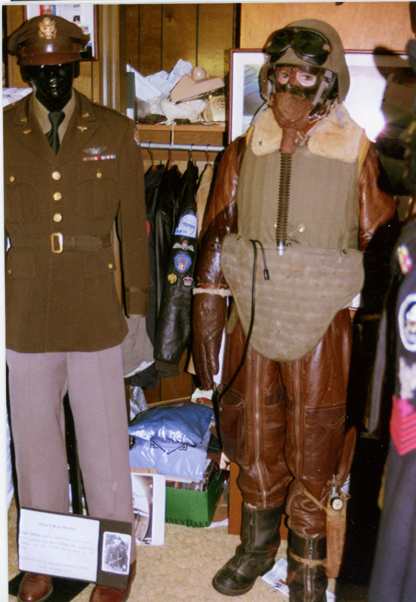 On the left, a uniform worn by Clark Gable during his WWII service. On the right, a high altitude bomber machine gunner's flight suit.