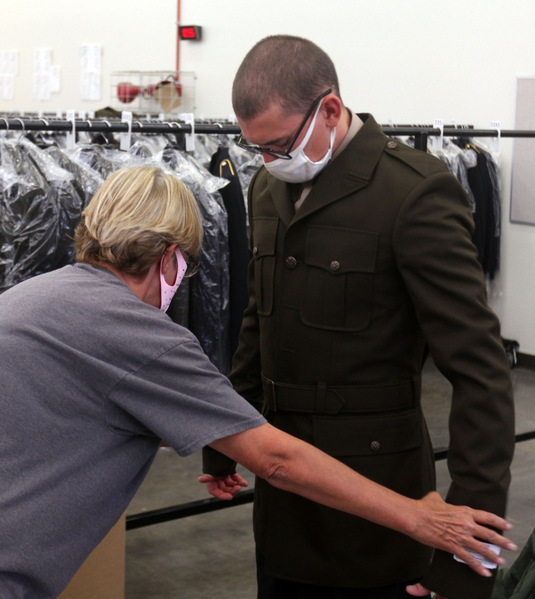 Donna Smith, supervisor of the Clothing Initial Issue Point inside Vessey Hall, gets Pvt. Andrew Fraughton of A Battery, 1st Battalion, 79th Field Artillery fitted for the jacket of the Army Green Service Uniform Oct. 14, 2020.
