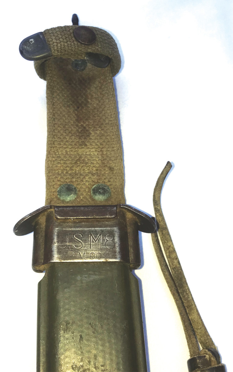 A closer look at the designation and manufacturer mark stamped into the metal. Note the right -over-left retaining strap. This is the style used on the early M8 scabbards.