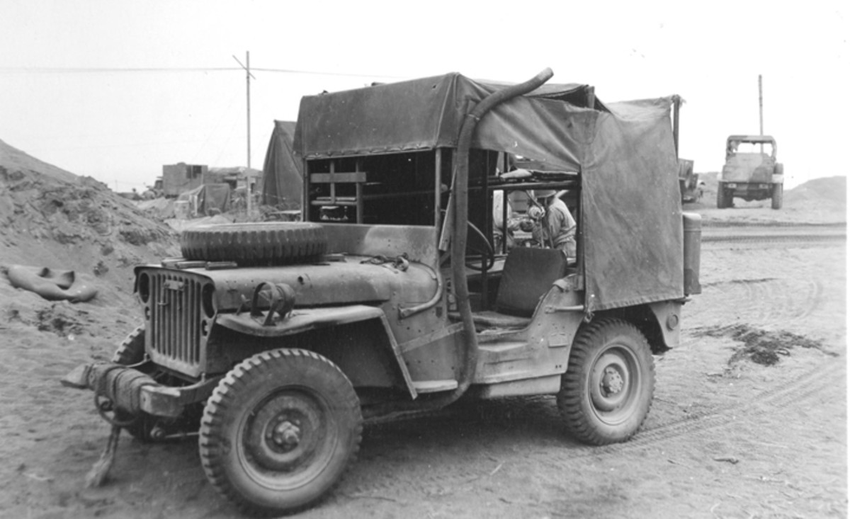 Canvas ripped and sagging, windshield glazing gone, and fenders battered, this Holden Jeep shows the rigors of combat on Iwo Jima, where this photo was taken. Note the extended exhaust for fording, and the shrapnel-caused hole in the hood. National Archives